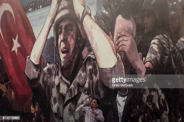 A man takes a photograph in front of a large billboard displaying a painted poster depicting the events of the July 15 2016 coup attempt ahead of the...