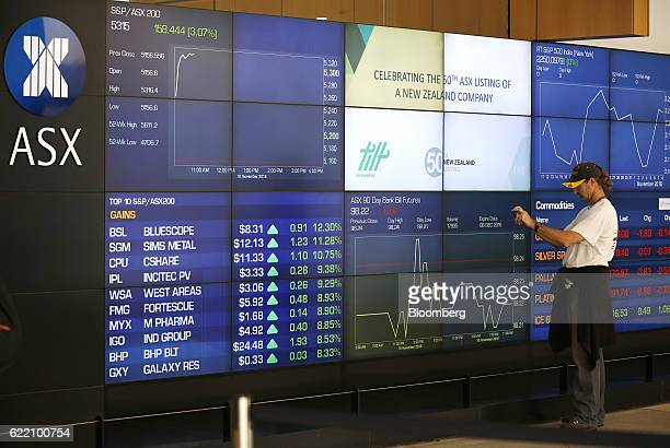 A man takes a photograph in front of an electronic board displaying stock information inside the Australian Securities Exchange operated by ASX Ltd...