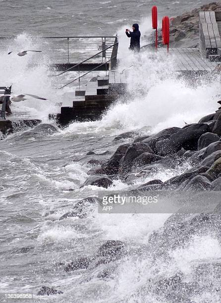 A man takes a photograph in Malmo harbour as the latest winterstorm hit the Swedish coast on January 4 2012 Winds of 31 metres per second were...