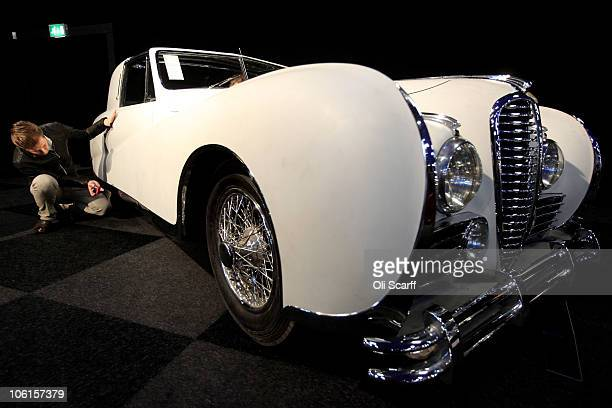 A man takes a photograph of a 1948 Delahaye 175S Coupe de Ville Aerodynamic Body with an estimated sale price of 120000 GBP prior to the 'Automobiles...