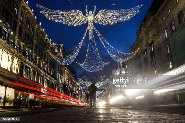 A man takes a photograph of a Christmas light display on Regent Street on December 15 2017 in London England