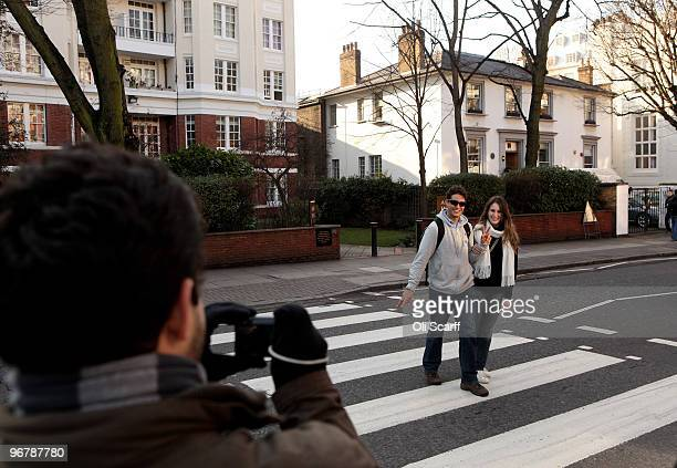 A man takes a photograph of a couple using the zebra crossing in front of the Abbey Road recording studios which have been put up for sale by their...