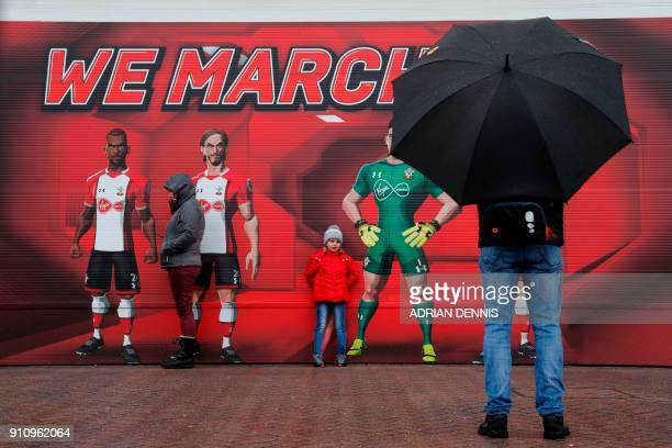 A man takes a photograph of a girl against a wall outside the stadium adorned with a message to 'We March On' ahead of kick off of the English FA Cup...
