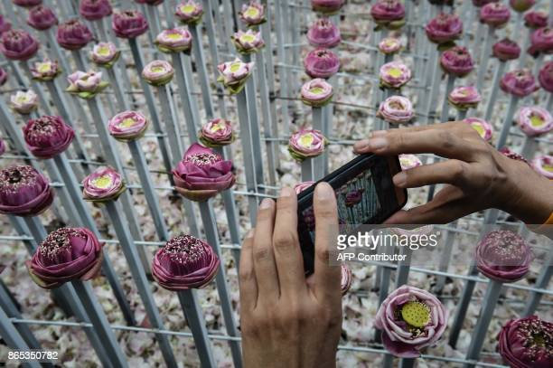 A man takes a photograph of a lotus flower display made in honour of the late Thai king Bhumibol Adulyadej at Pak Khlong Talad flower market in...