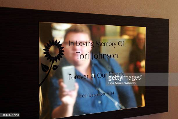 A man takes a photograph of a memorial for Tori Johnson at the Lindt Cafe in Martin Place on March 20 2015 in Sydney Australia The cafe reopened to...