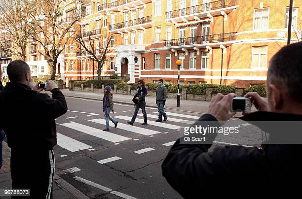A man takes a photograph of a people using the zebra crossing in front of the Abbey Road recording studios which have been put up for sale by their...