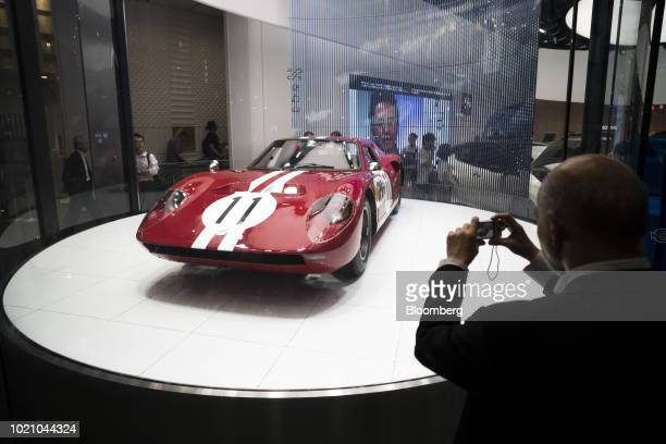A man takes a photograph of a Prince Motor Co R380 racing car displayed at a Nissan Motor Co's showroom in the Ginza area of Tokyo Japan on Tuesday...