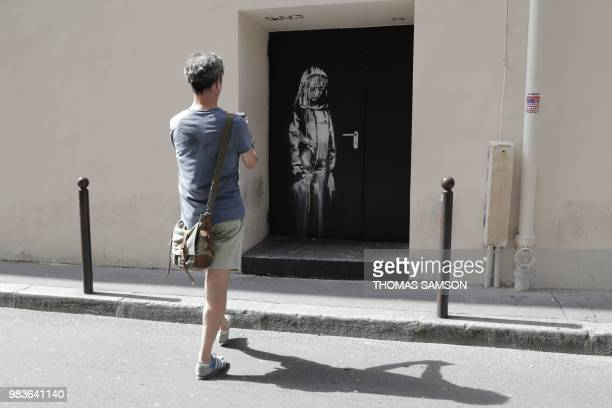 A man takes a photograph of a recent artwork by street artist Banksy in Paris on June 25 on a side street to the Bataclan concert hall where a...