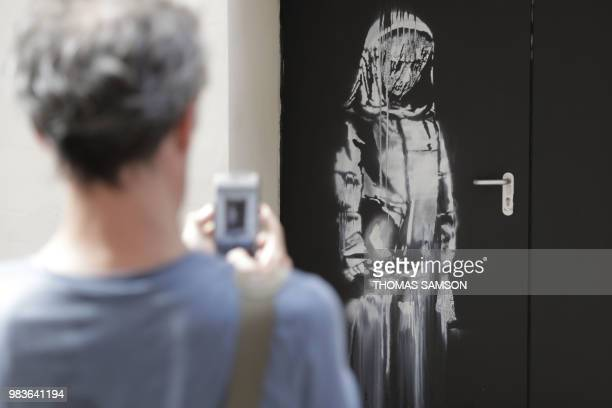 TOPSHOT A man takes a photograph of a recent artwork by street artist Banksy in Paris on June 25 on a side street to the Bataclan concert hall where...