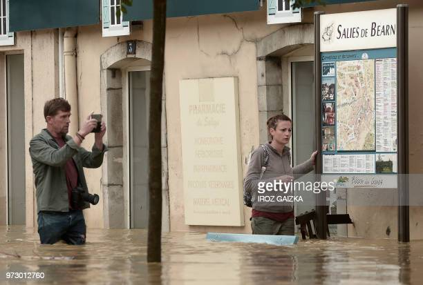 A man takes a photograph of a woman as they stand in flood waters that swept through the streets following heavy rains in SaliesdeBearn south western...