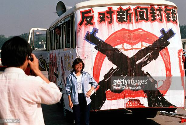 A man takes a photograph of a woman standing next to a bus painted with protest slogans parked in Tiananmen Square Prodemocracy demonstrators and...