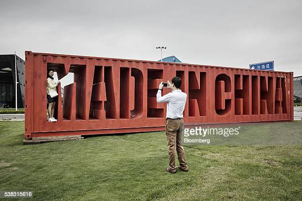 A man takes a photograph of a woman standing with a sign reading Made In China at the China Guangdong Pilot Free Trade Zone in Shenzhen Guangdong...