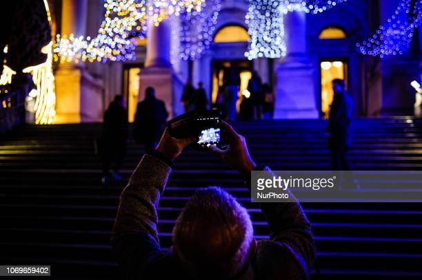 A man takes a photograph of artist Monster Chetwynd's giant illuminated slugs installation on the facade of the Tate Britain art gallery in London...
