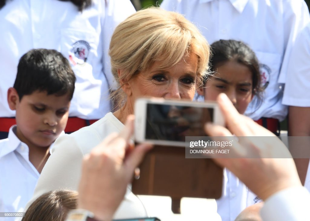 A man takes a photograph of Brigitte Macron, the wife of the French President Emmanuel Macron, during a meeting with members of the French community living in India at the French embassy in New Delhi on March 11, 2018. Brigitte Macron is visiting India with her husband on an official three-day state visit where they will travel to New Delhi, Agra and Varanasi. /