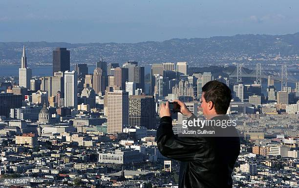 A man takes a photograph of downtown San Francisco from Twin Peaks March 25 2005 in San Francisco California San Francisco's 49Mile Scenic Drive was...