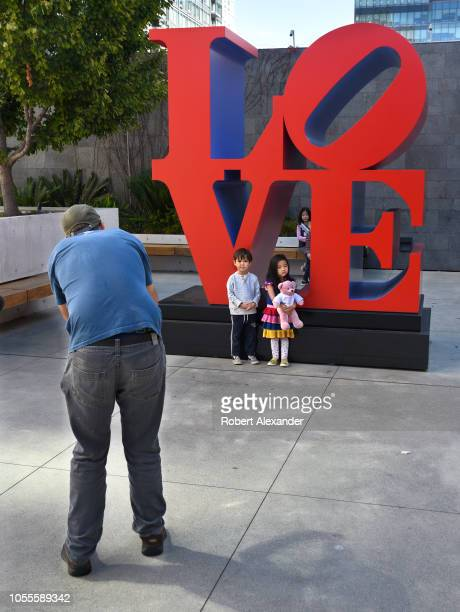 SAN FRANCISCO CALIFORNIA SEPTEMBER 16 2018 A man takes a photograph of his two children as they stand in front of Robert Indiana's sculpture 'LOVE'...