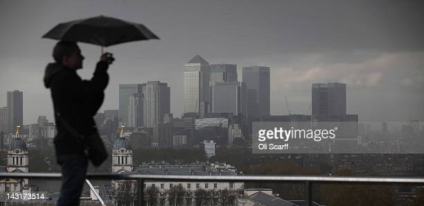 A man takes a photograph of the City of London in heavy rain in Greenwich Park on April 20 2012 in London England Many areas of the UK have...