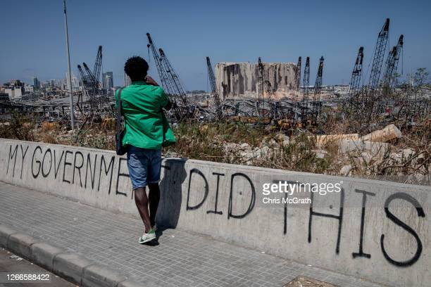 Man takes a photograph of the destroyed Beirut port on August 16, 2020 in Beirut, Lebanon. The explosion at Beirut's port last week killed over 200...