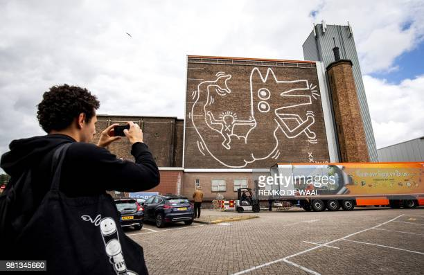 A man takes a photograph of the giant mural painted by the American artist Keith Haring in 1986 on the wall of the former depot of the Stedelijk...