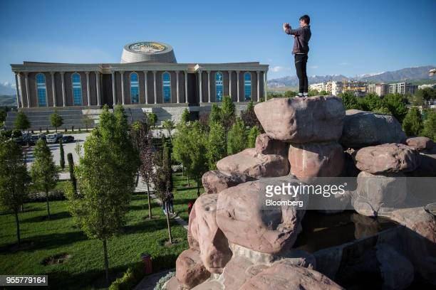 A man takes a photograph of the National Museum of Tajikistan while standing atop a pile of rocks in Dushanbe Tajikistan on Saturday April 21 2018...