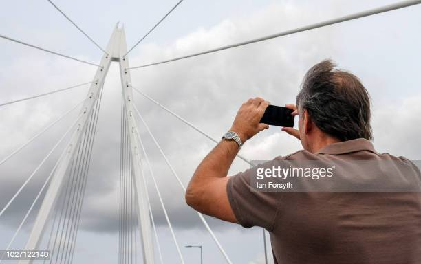 A man takes a photograph of the new Northern Spire bridge spanning the River Wear as it opens for a pedestrian walkover on August 28 2018 in...