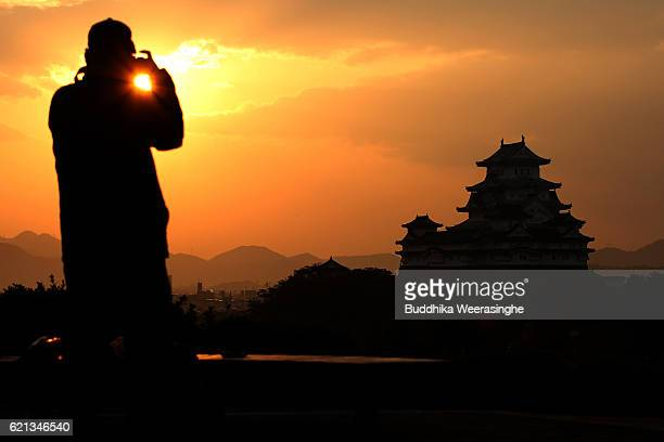HIMEJI JAPAN NOVEMBER 6 A man takes a photograph of the sunrise over the UNESCO World Heritage site Himeji Castle on November 6 2016 in Himeji Japan...