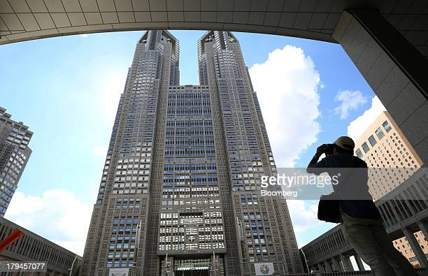 Man takes a photograph of the Tokyo Metropolitan City Hall in the Shinjuku district of Tokyo, Japan, on Tuesday, Sept. 3, 2013. Tokyo is the odds-on...