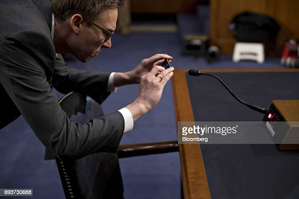 Man takes a photograph of the witness microphone in the Senate Intelligence Committee hearing room ahead of testimony by former Federal Bureau of...