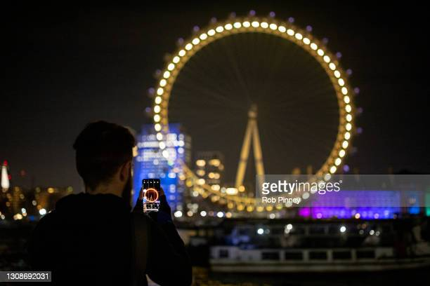Man takes a photograph on his mobile phone of the London Eye illuminated in yellow on March 23, 2021 in London, England. Marie Curie Cancer Charity...