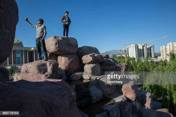 A man takes a photograph while standing atop a pile of rocks at the National Museum of Tajikistan left as cranes stand at a construction site in the...