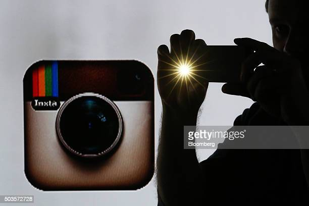 A man takes a photograph with a mobile device whilst standing against an illuminated wall bearing Instagram Inc's logo in this arranged photograph in...