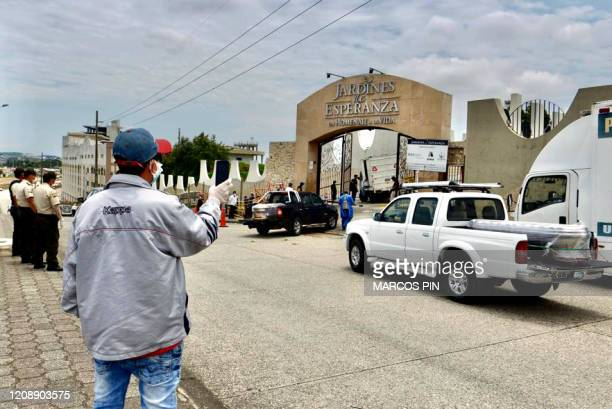 A man takes a picture as coffins are transported into a cemetery on trucks in Guayaquil Ecuador on April 1 2020 Residents of Guayaquil in Ecuador's...