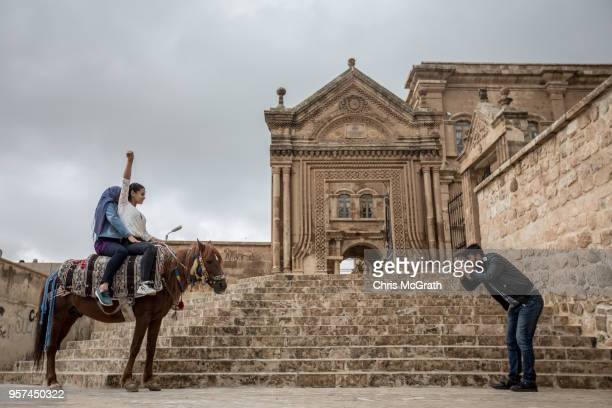 Tourists visit Kasimiye Madrasah on the outskirts of the Old City of Mardin on May 11 2018 in Mardin Turkey Mardin a historical city in South Eastern...