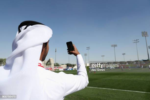 A man takes a picture during a training session on day 2 of the FC Bayern Muenchen training camp at ASPIRE Academy for Sports Excellence on January 3...