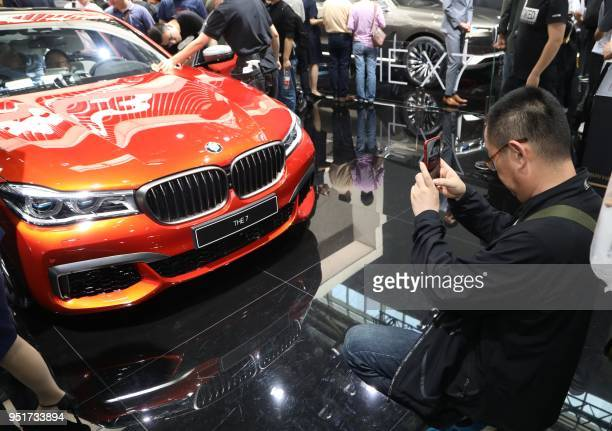 A man takes a picture of a BMW THE 7 during the first public opening day at the Beijing auto show in Beijing on April 27 2018 / China OUT