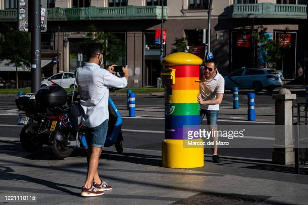 Man takes a picture of a friend who hides behind a mailbox painted with the Rainbow LGTB colors. The Spanish Postal Service has painted some...
