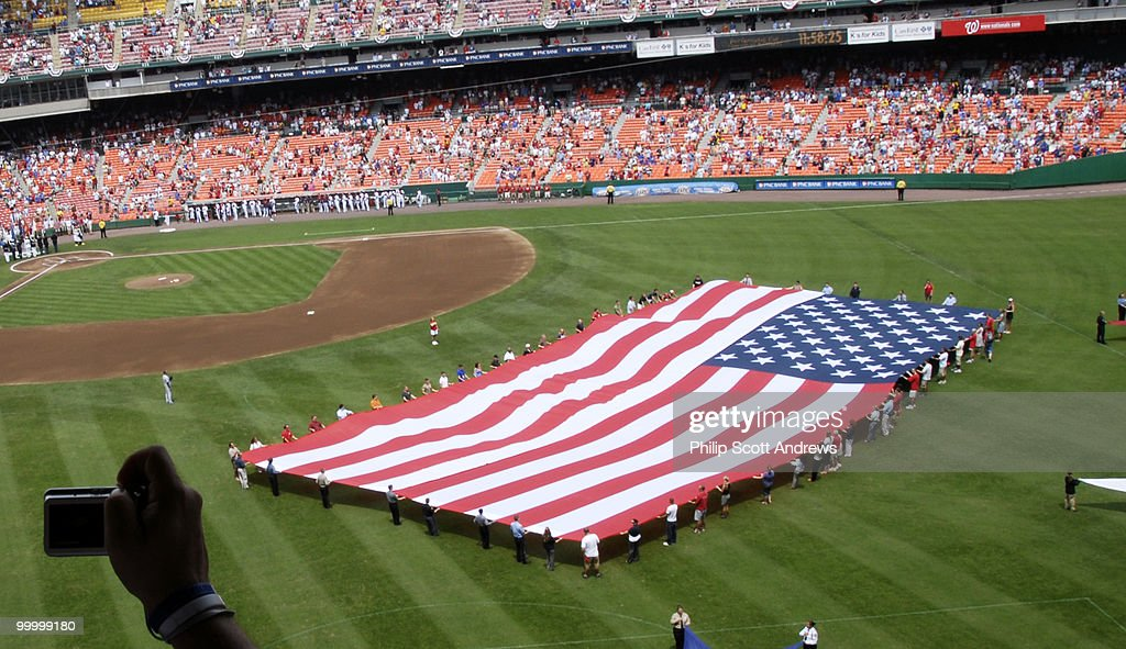 A man takes a picture of a giant American flag at RFK stadium before the start of the July 4th game between the Washington Nationals and the Chicago Cubs. The Nationals beat the cubs 6-0 with two home runs including a grand slam.