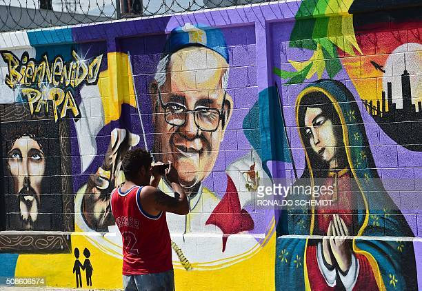 A man takes a picture of a graffiti welcoming Pope Francis to Ecatepec on the north east side of Mexico City on February 5 2016 The Pope will visit...