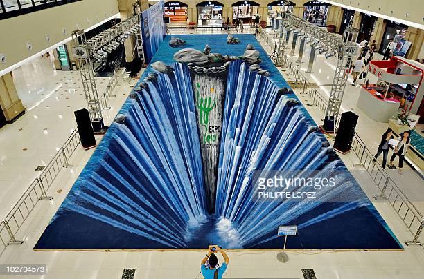A man takes a picture of a huge threedimensional painting made on the floor of a shopping mall by German artist Edgar Muller in Shanghai on August 6...