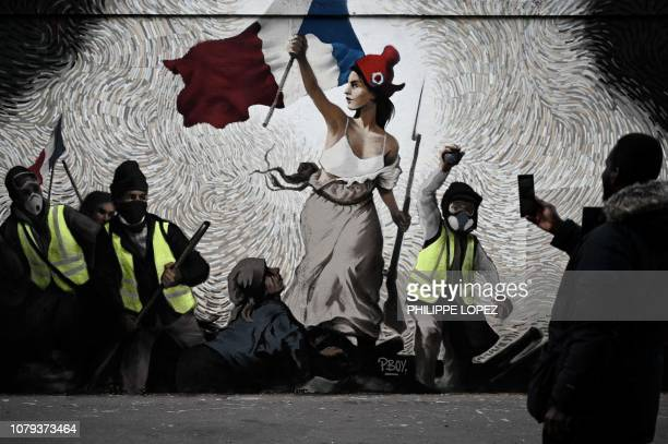 """Man takes a picture of a mural by street artist PBOY depicting Yellow Vest protestors inspired by """"La Liberte guidant le Peuple"""" painting by Eugene..."""