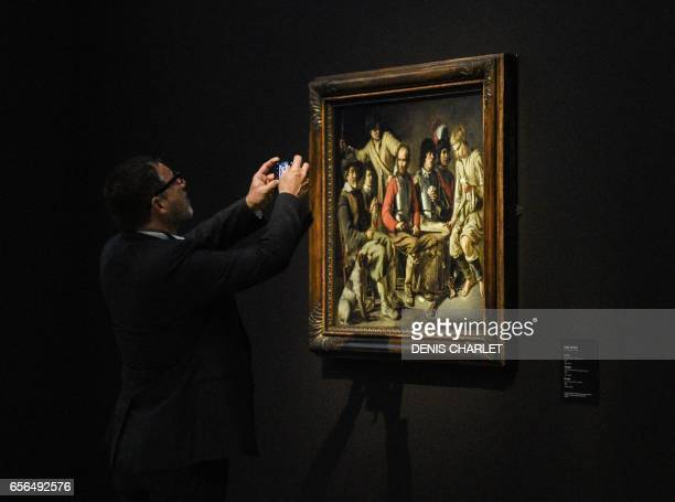 A man takes a picture of a painting by French painter Louis Le Nain presented during the exhibtion 'Le mystere Le Nain' at the LouvreLens in Lens...