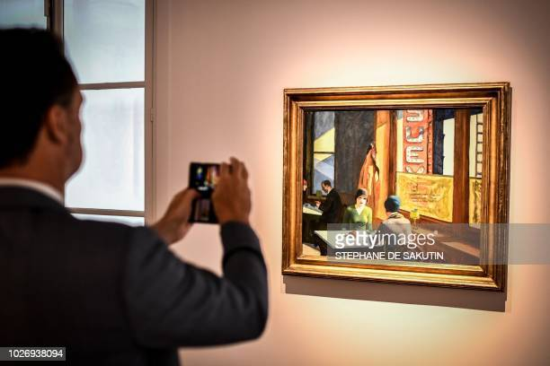 A man takes a picture of a painting by US artist Edward Hopper named Chop Suey that is part of the Barney A Ebsworth Collection during a presentation...