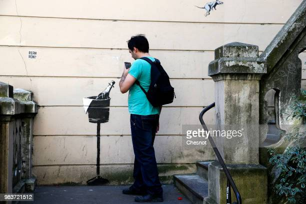 A woman walks past a recent artwork attributed to street artist Banksy on June 25 2018 in Paris France Six frescoes attributed to Banksy were...