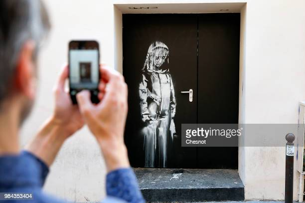 A man takes a picture of a recent artwork attributed to street artist Banksy on June 26 2018 in Paris France Yesterday a new artwork attributed to...