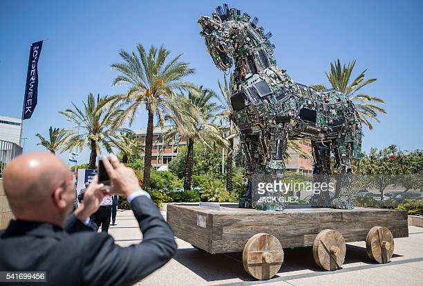 A man takes a picture of a replica of the Trojan horse designed by 'No No No No No Yes' and made up of thousands of computer and mobile phone...