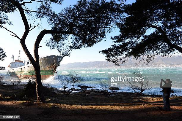 A man takes a picture of a ship that ran aground after a storm near the Adriatic city of Split on March 6 2015 Winds in the Croatian coastal city of...