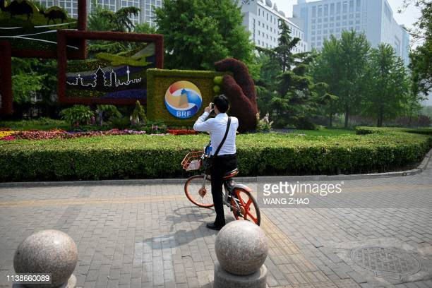 A man takes a picture of a sign promoting the Belt and Road Forum in Beijing on April 22 2019