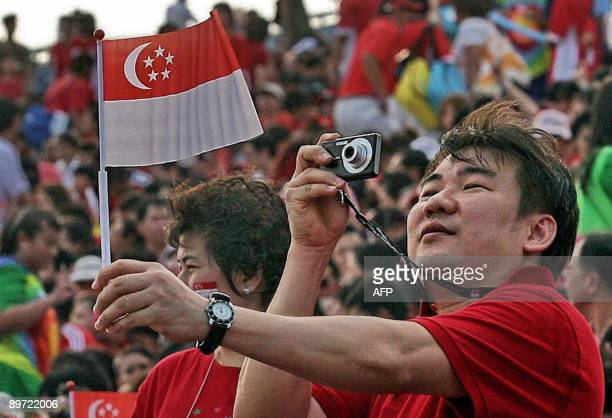 A man takes a picture of a Singapore flag at an event to mark the island nation's 44th National Day on August 9 2009 In his National Day message...