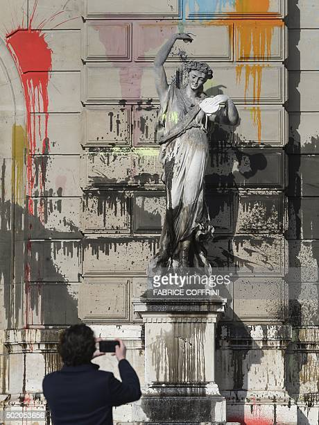 A man takes a picture of a statue outside the Grand Theatre de Geneve opera house on December 20 2015 in Geneva after it was vandalised during a...