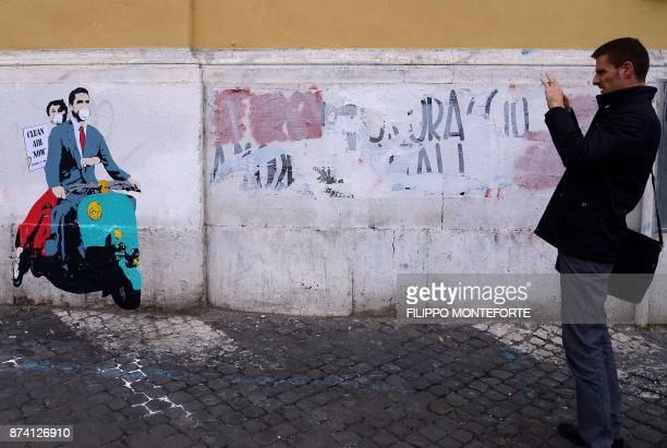 A man takes a picture of a stencil by street artist TVboy depicting a scene of the 1953 movie Roman Holiday with US actors Gregory Peck and Audrey...